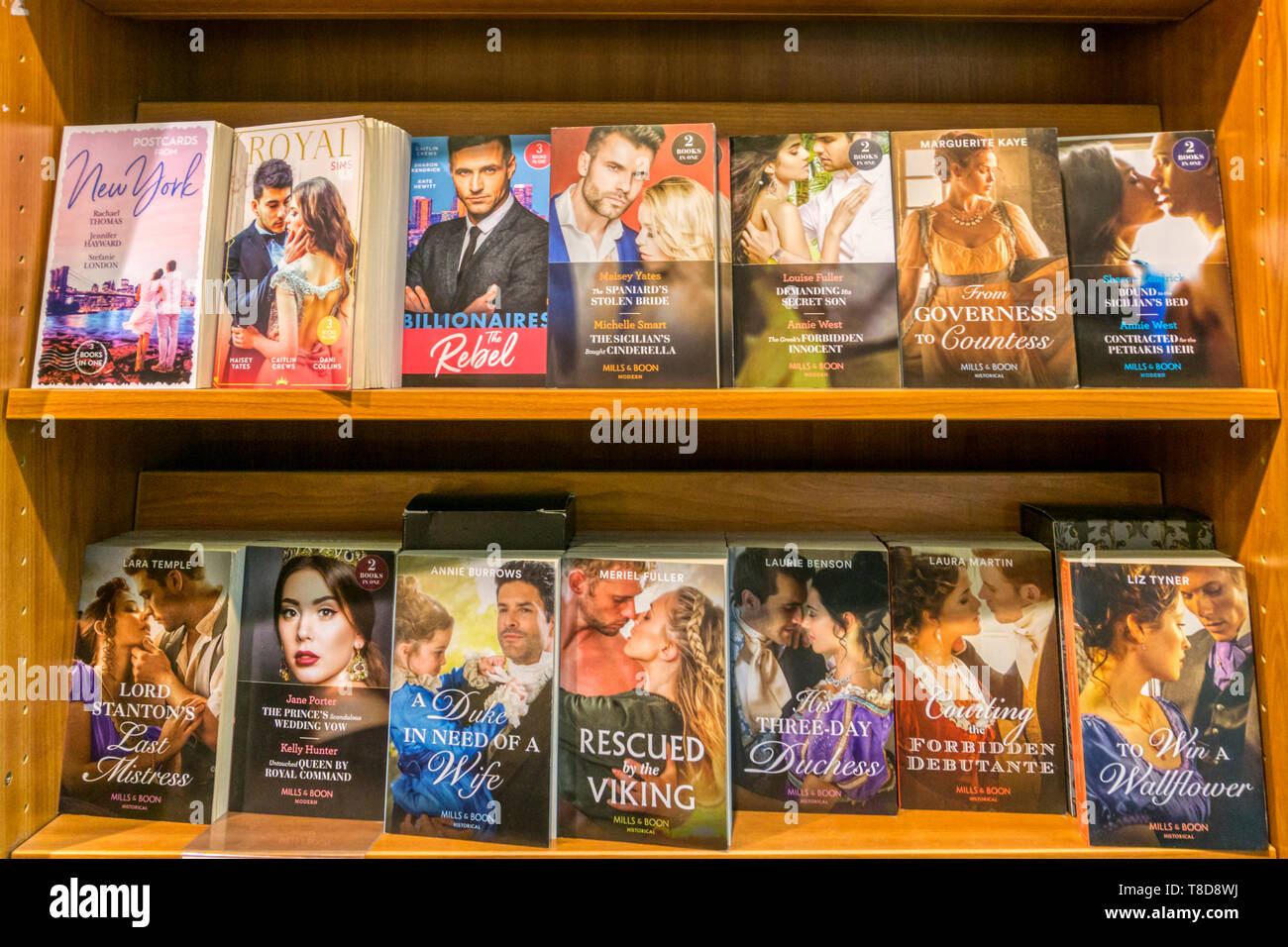 A selection of Mills & Boon paperback romantic novels and historical romances displayed for sale in a bookshop. - Stock Image