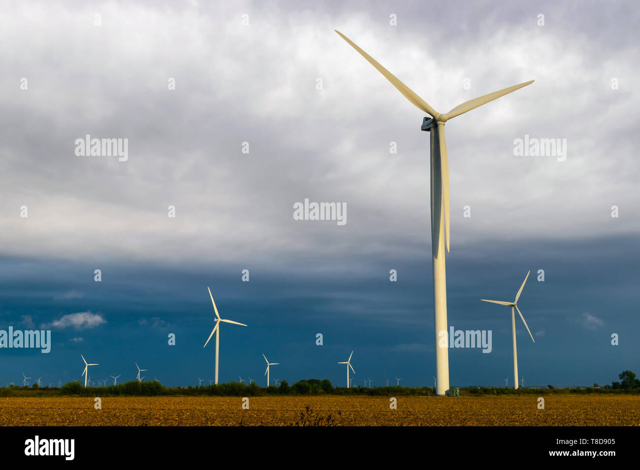 Wind Turbine during a cloudy day on a farm. - Stock Image