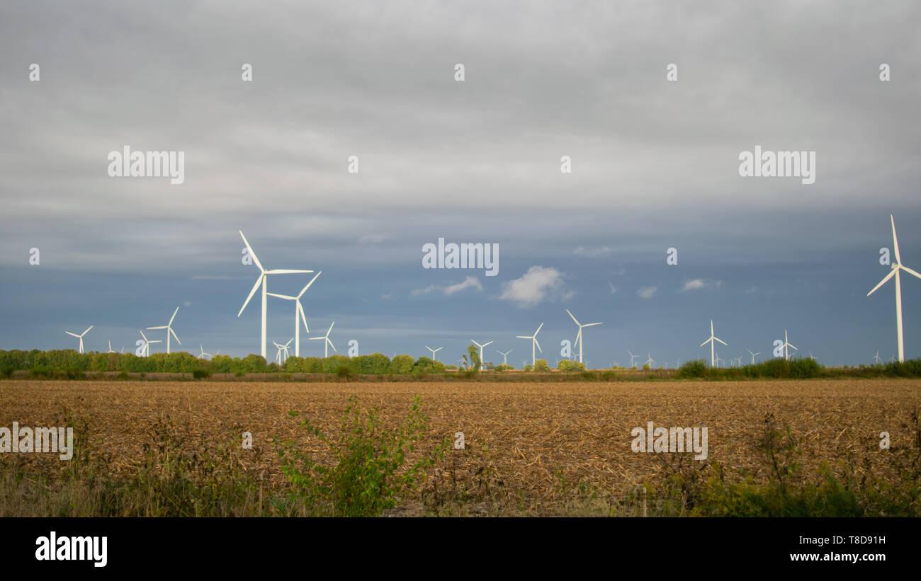 Wind Turbine farm on a cloudy day in an open field. - Stock Image