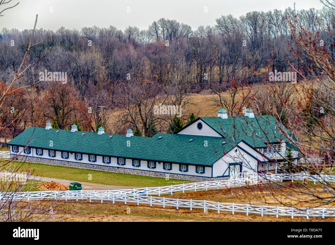 A horse ranch/horse farm/stable with a white wooden fence in Michigan, USA. - Stock Image