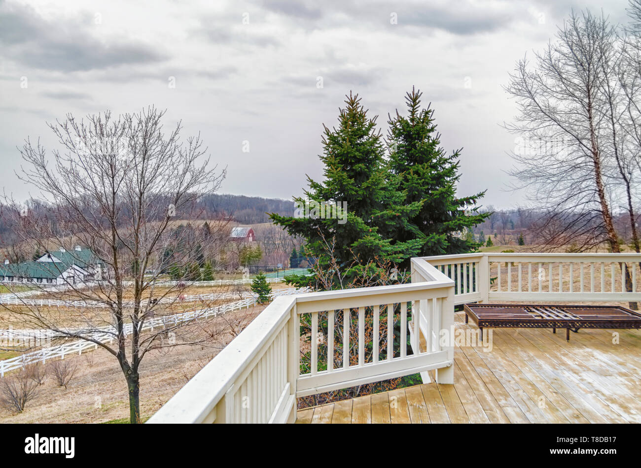 A view from the rear deck of a home. Signs of Spring in the air: tree buds and other emergences. A horse ranch can be seen in the distance. - Stock Image