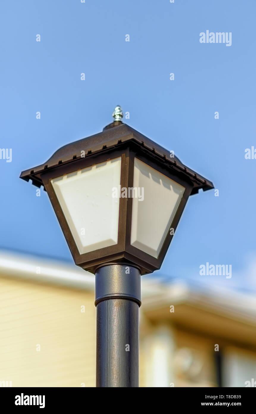 An unlit street lamp/streetlamp/street light/streetlight on a bright and sunny day. - Stock Image