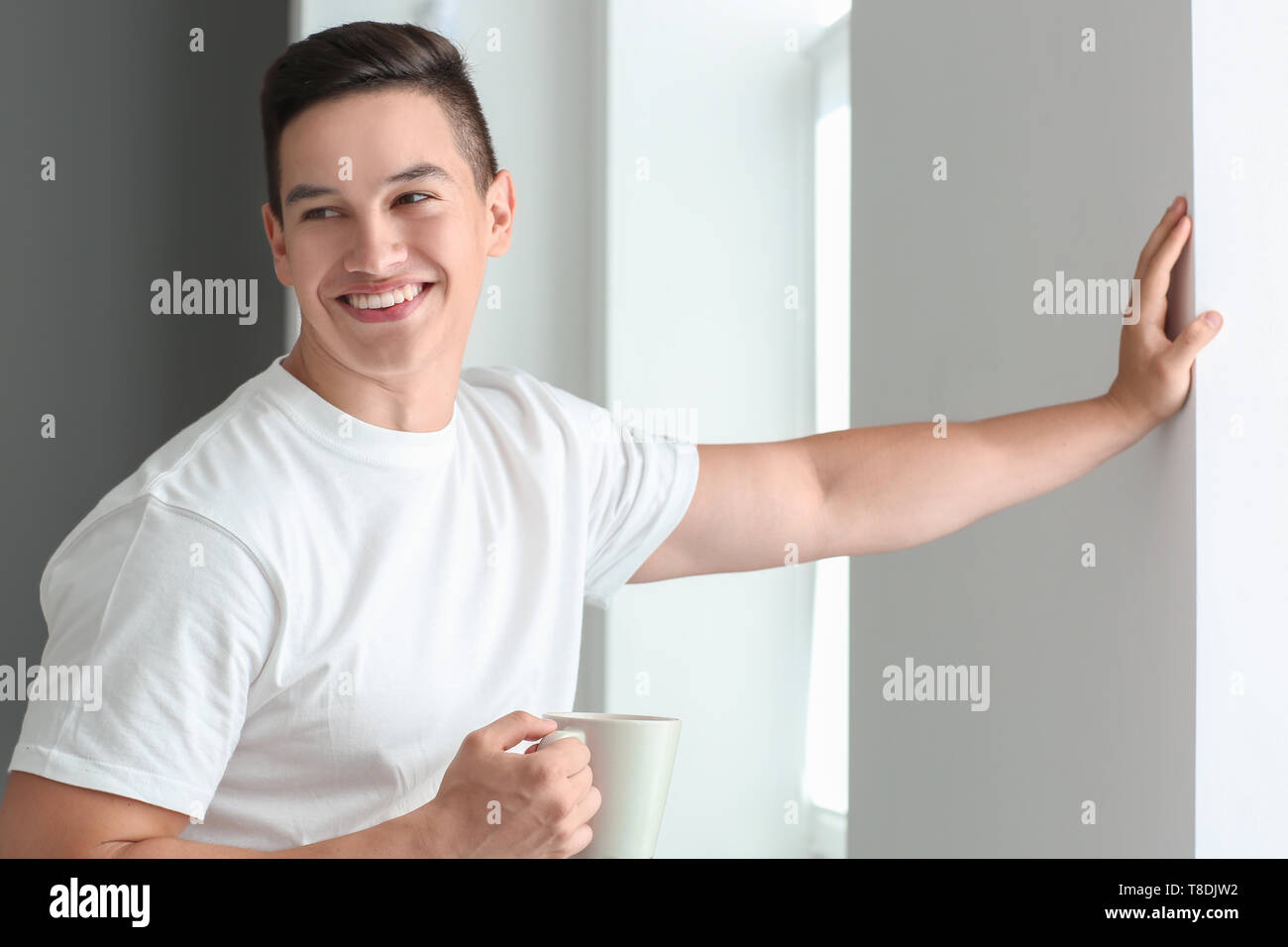 Handsome young man with cup of coffee near window - Stock Image