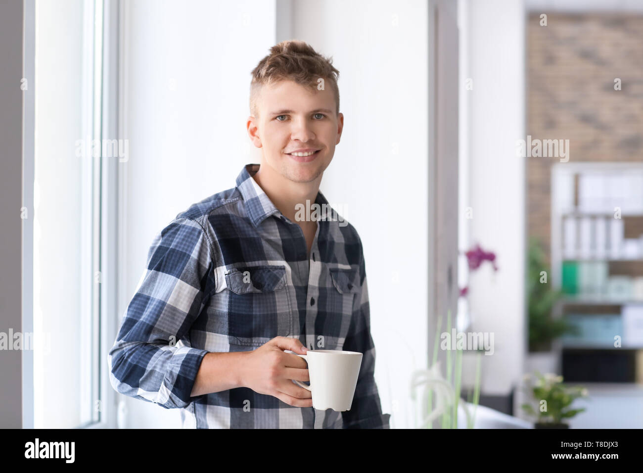 Portrait of handsome young man with cup of coffee near window - Stock Image