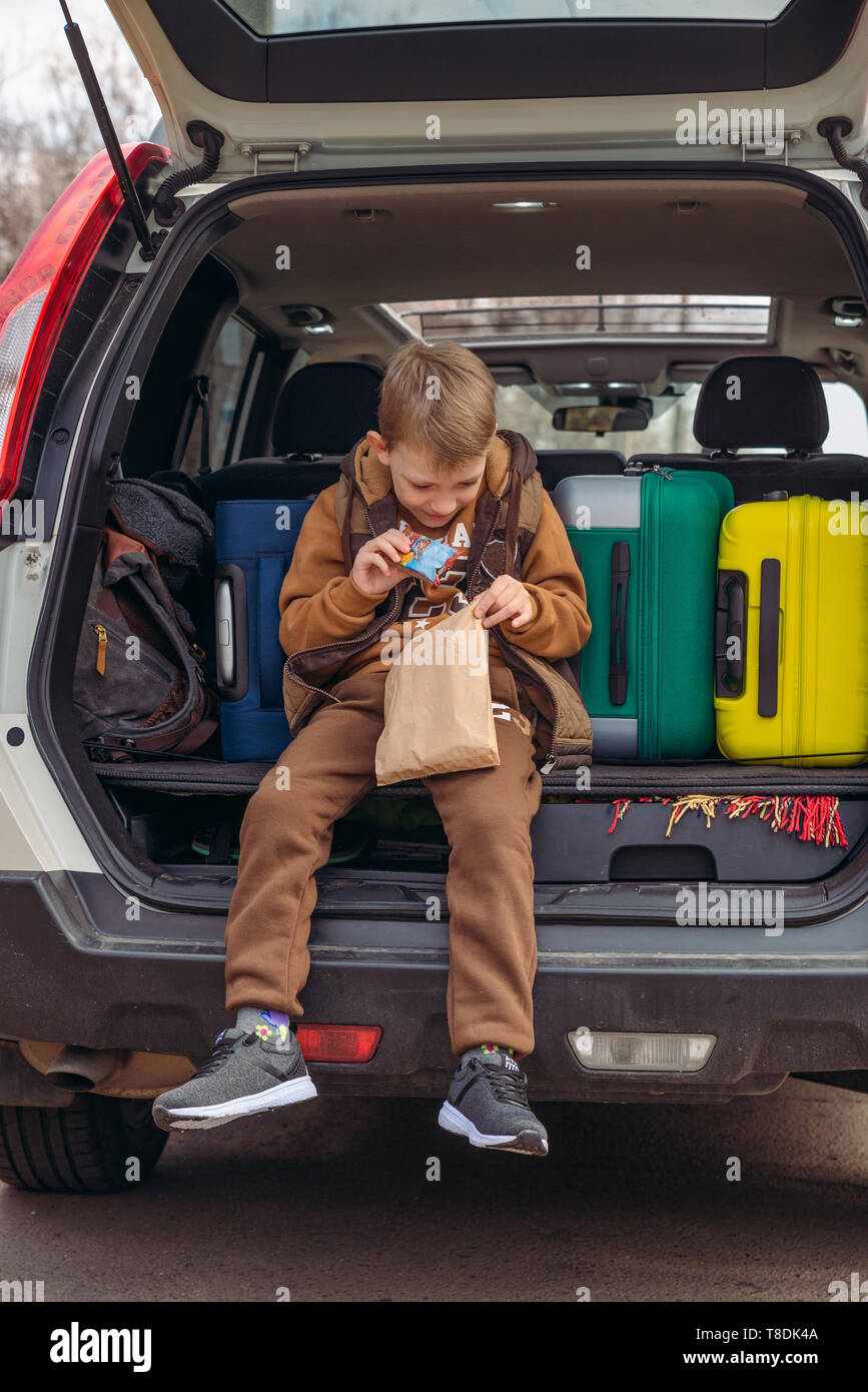 little kid looking into paper bag with candies sitting in car trunk full of bags. Stock Photo