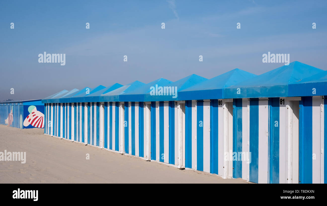 Blue and white striped beach huts on the sand on the sea front at Malo-Les-Bains beach in Dunkirk, France Stock Photo