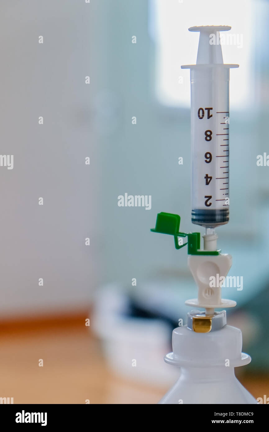 Medical syringe in the vial, defocused background, medical and healthcare concept, medicinal device, equipment - Stock Image