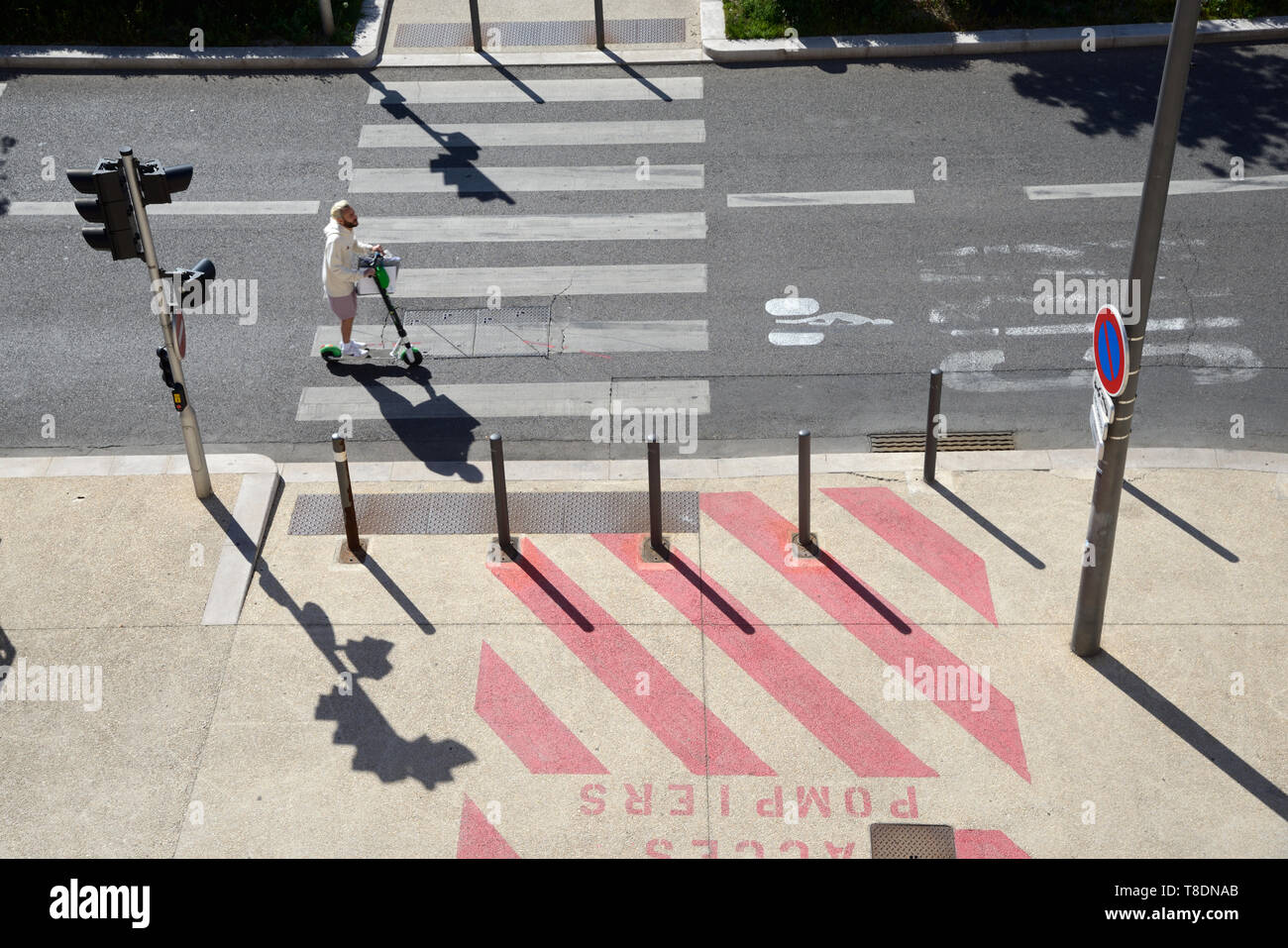 Rider on Stand-Up Scooter or Motorised Kick Scooter Riding in Cycle Lane or Bike Lane with Road Markings & Pedestrian Crossing Marseille France - Stock Image