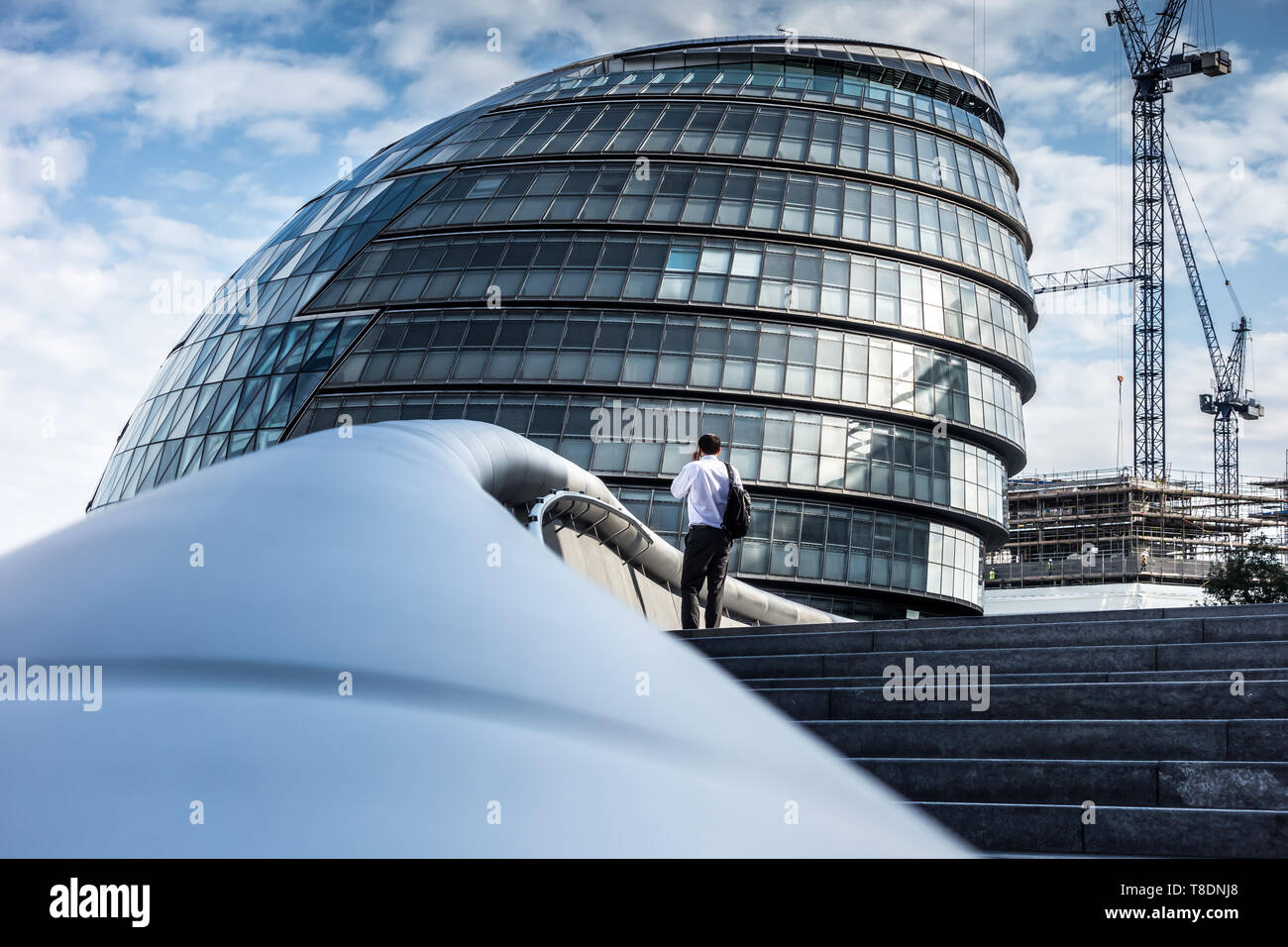 Man on Mobile phone standing on the steps of City Hall London Stock Photo