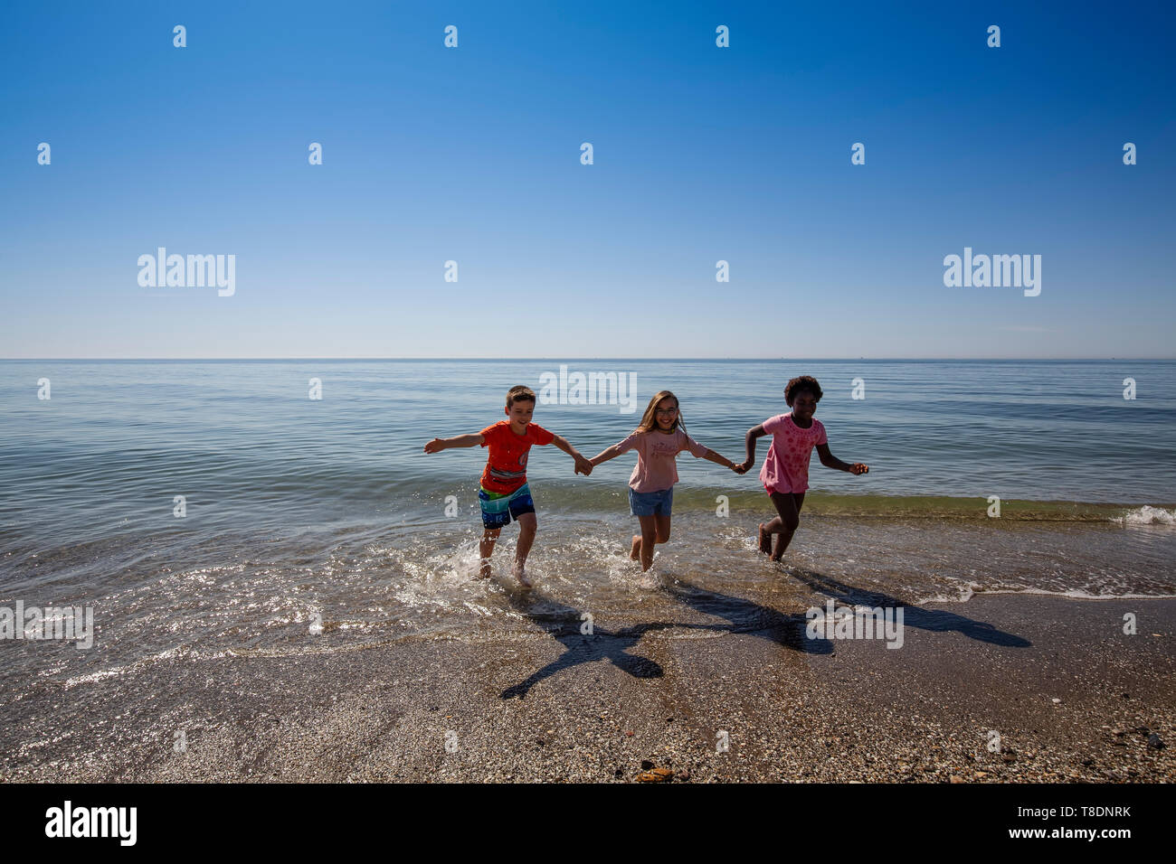 Group of children having fun on the beach. Mediterranean sea and blue sky. Costa del Sol, Marbella. Andalusia, Southern Spain. Europe - Stock Image