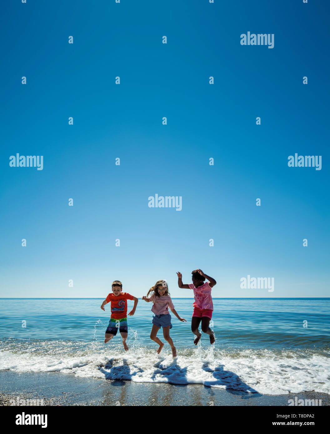 Group of children having fun on the beach. Mediterranean sea and blue sky. Costa del Sol, Marbella. Andalusia, Southern Spain. Europe Stock Photo