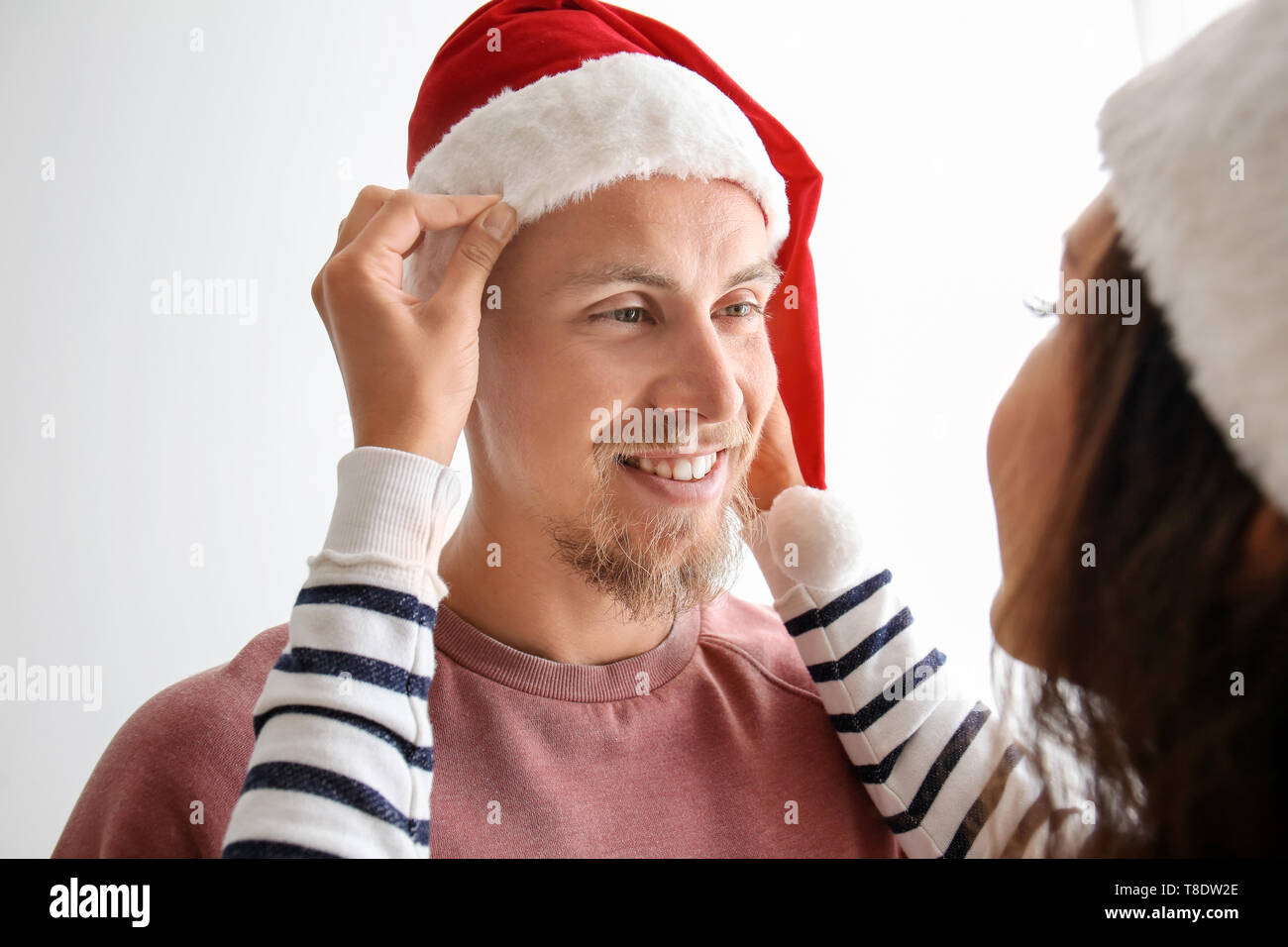 ac0011c4 Young woman helping her boyfriend to put on Santa hat against white  background