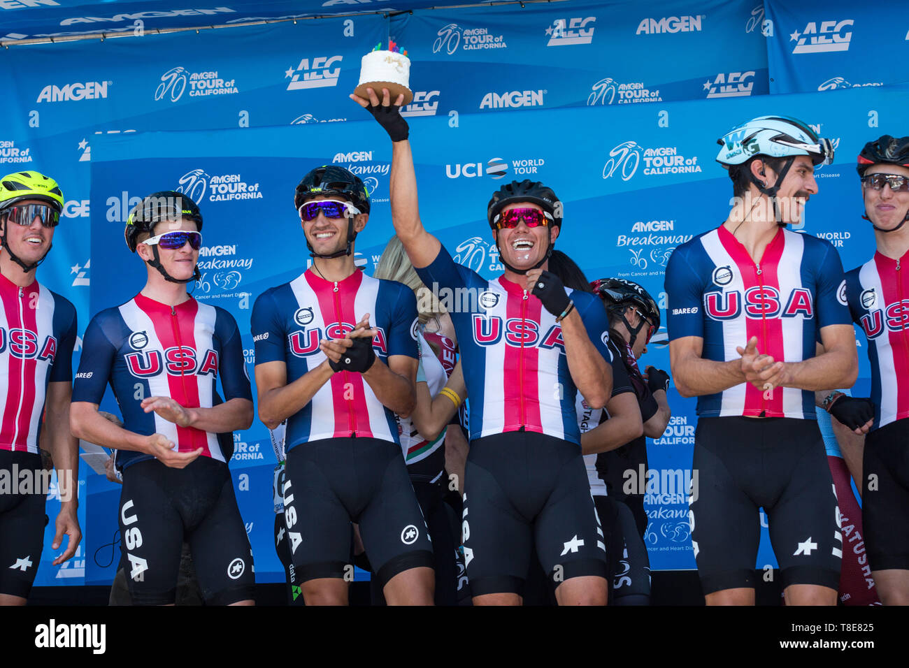 Sacramento, California, USA. 12th May, 2019. TRAVIS MCCABE lifts his birthday cake as Team USA is introduced prior to Stage 1 of the 2019 Amgen Tour of California at California's State Capitol city of Sacramento on Sunday afternoon. Stage 1 begins and ends in Sacramento, where the American and Sacramento Rivers meet before heading west. This is the race's 10th year in Sacramento.The 2019 Amgen Tour of California race will showcase scenic California roadways, coastlines and iconic settings, with more than 750 miles of racing throughout the seven-day event. The race will run north to south th - Stock Image