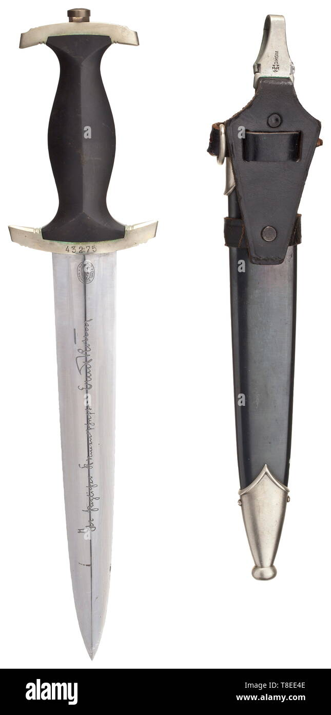 """An SS honour dagger M 34 with Röhm dedication The blade with obverse etched device """"Meine Ehre Heißt Treue""""(tr. """"My honour is loyalty""""), the reverse with the logo of Eickhorn, Solingen and dedication """"In herzlicher Kameradschaft Ernst Röhm"""". Black wooden grip with nickel silver national eagle and enamelled SS emblem. The grip fittings of non-ferrous metal, the cross-guard with struck """"III"""" surmounted by the SS number """"43275"""". Black burnished iron scabbard with silver-plated non-ferrous metal fittings, vertical hanger. Length 37 cm. A very rare and matching dagger in good co, Editorial-Use-Only Stock Photo"""