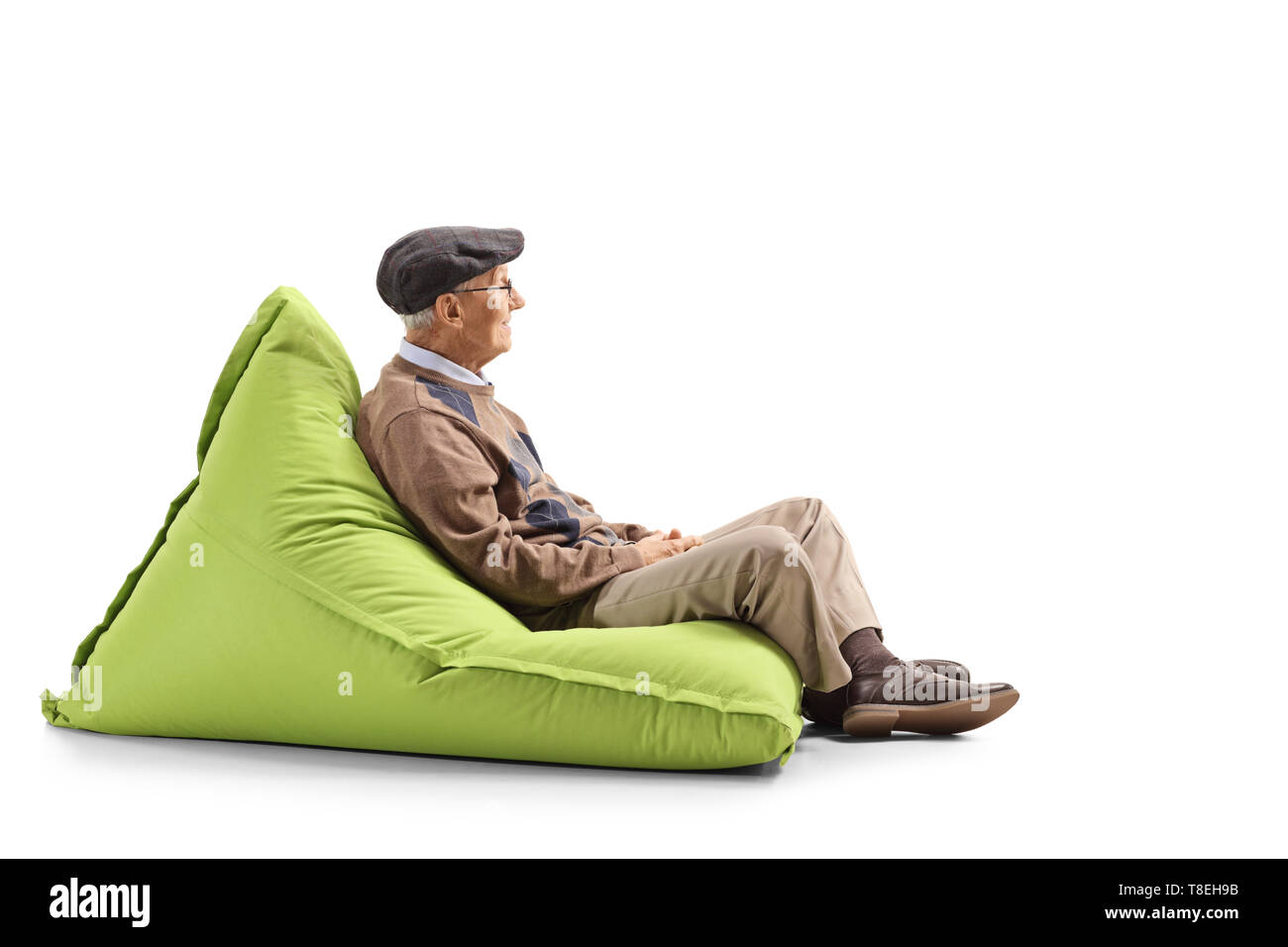 Full length profile shot of an elderly man sitting on a green bean bag isolated on white background - Stock Image