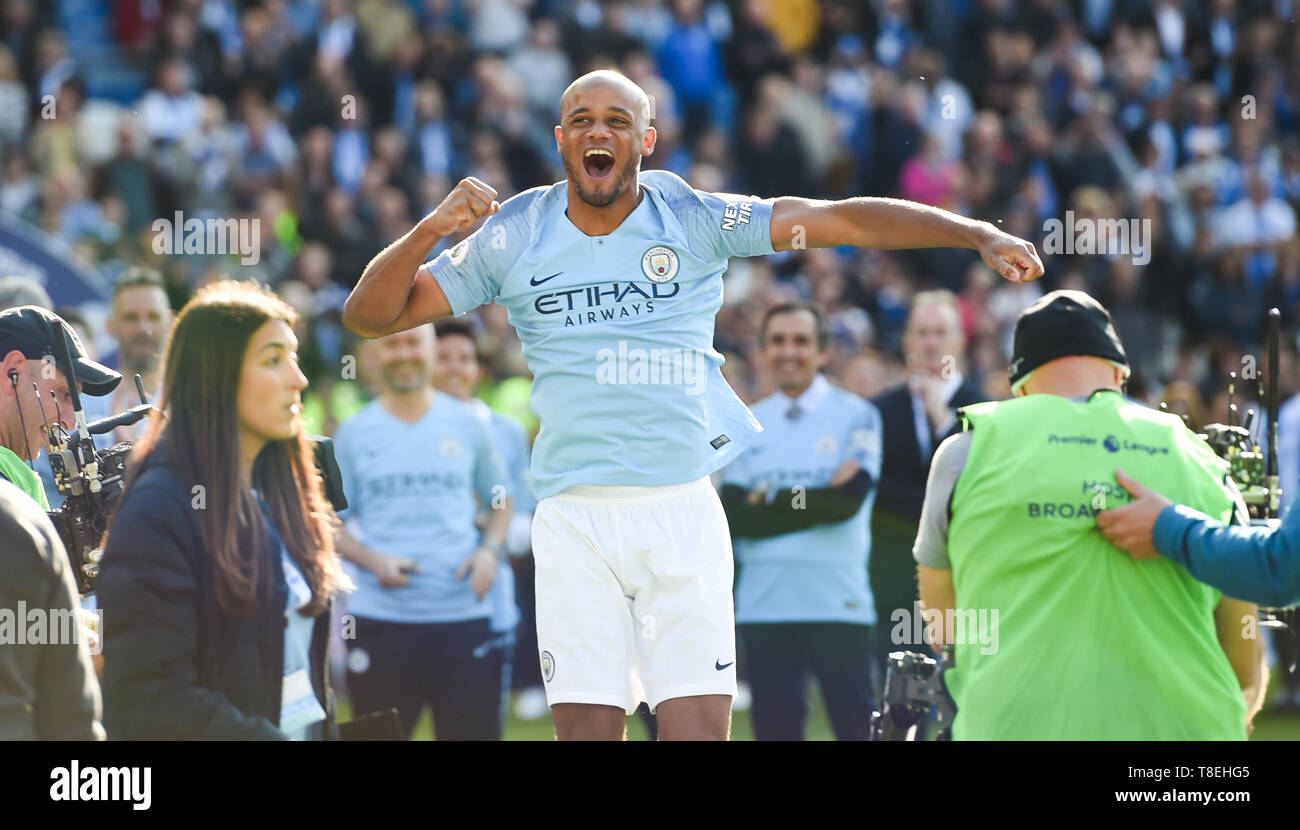 Vincent Kompany of Manchester City celebrates winning the title during the Premier League match between Brighton & Hove Albion and Manchester City  at the American Express Community Stadium 12 May 2019 Photograph taken by Simon Dack  Editorial use only. No merchandising. For Football images FA and Premier League restrictions apply inc. no internet/mobile usage without FAPL license - for details contact Football Dataco - Stock Image