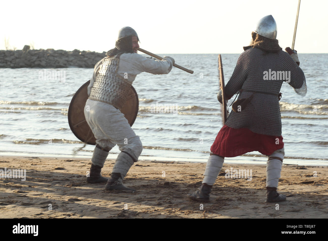 Two medieval Slav warriors are fighting with swords and shields on the beach - Stock Image