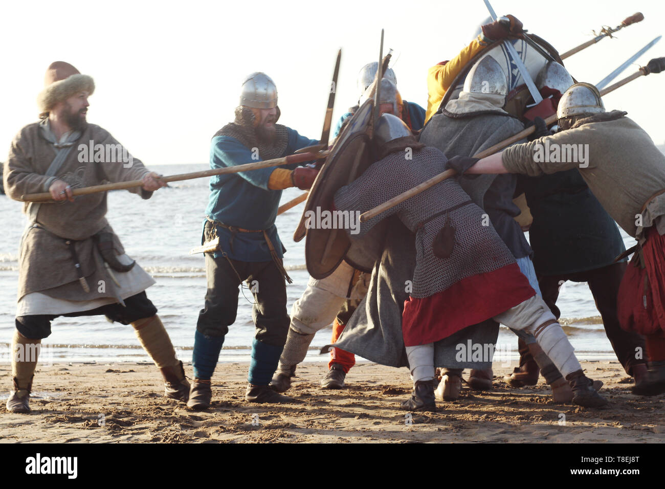 Slavic warriors reenactors with wearpons and shields training fighting outdoors at seaside - Stock Image
