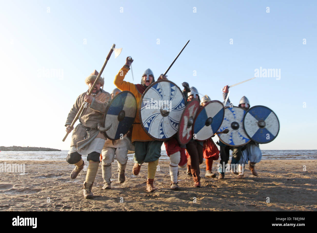 Slavic warriors reenactors with wearpons and shields training fighting outdoors at seaside , running at camera - Stock Image