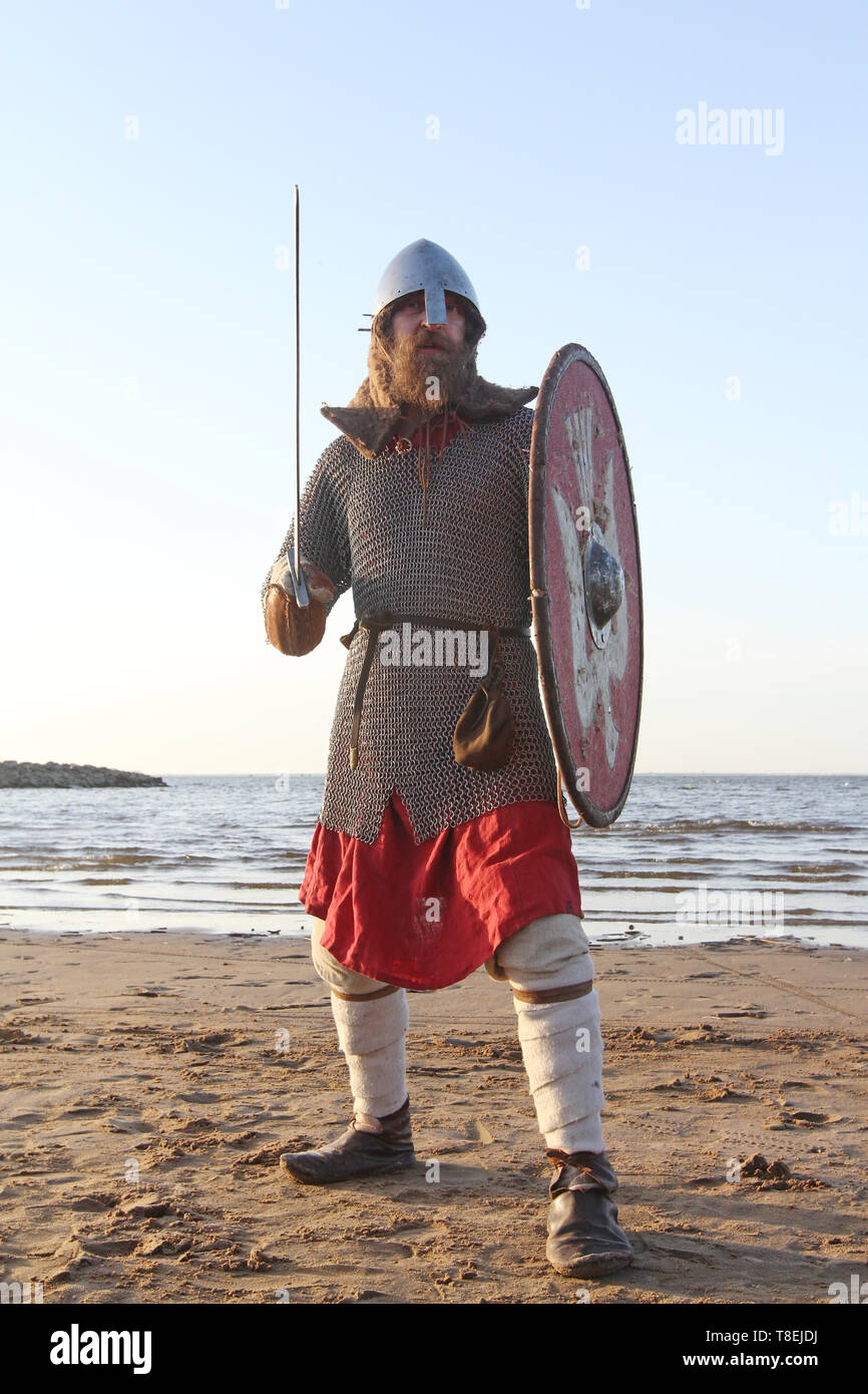 Portrait of slavic warrior reenactor with sword and shield posing outdoors at seaside - Stock Image