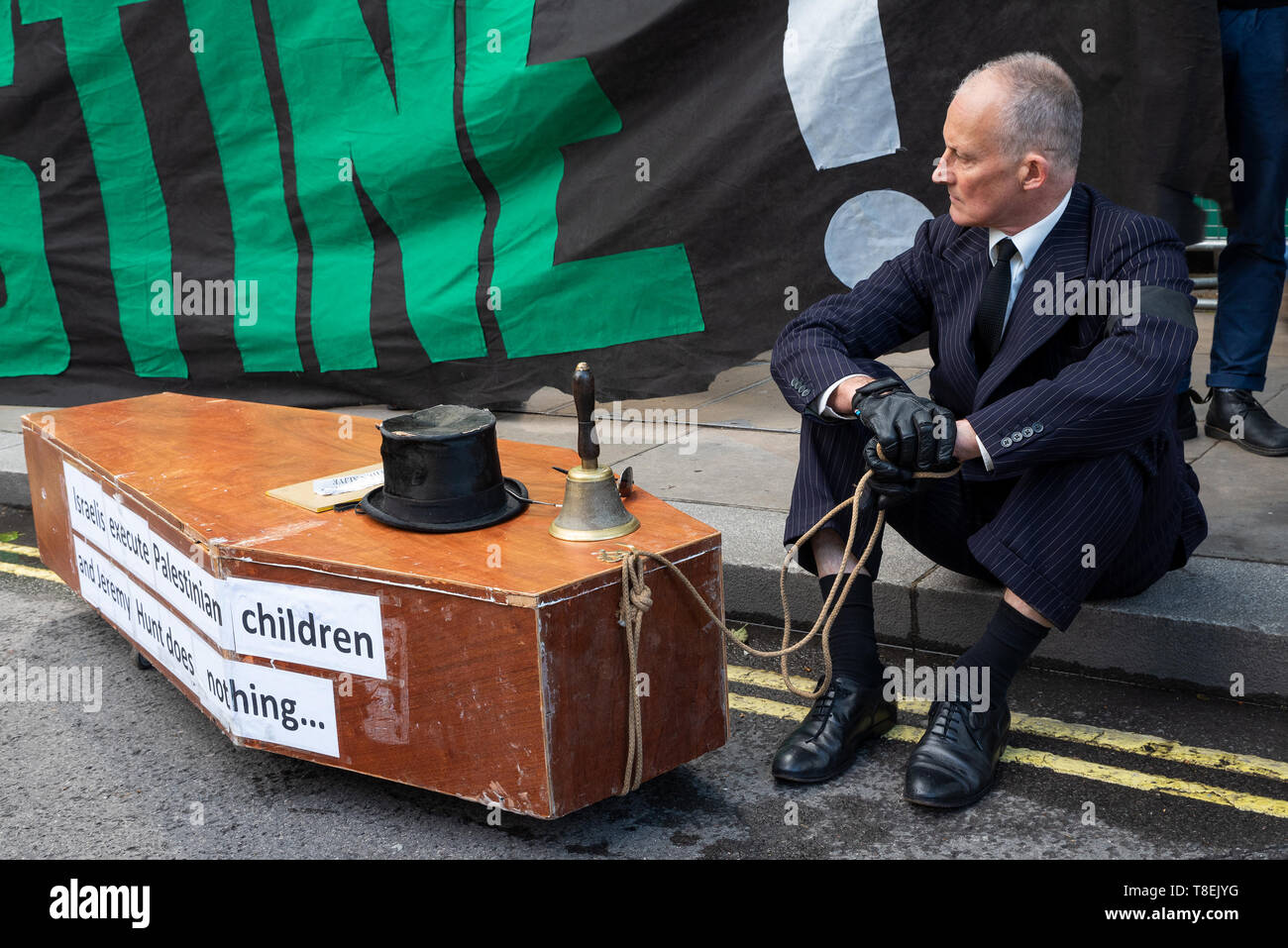London, UK. May 11th 2019. National Demonstration for Palestine. Thousands of activists marched from Portland Place to Whitehall. Organised by the Palestine Solidarity Campaign, Stop the War Coalition, Palestinian Forum in Britain, Friends of Al- Aqsa & Muslim Association of Britain. Pictured, Palestine activist sitting in Whitehall with coffin, with Israelis execute Palestinian children and Jeremy Hunt does nothing written on coffin side. Credit: Stephen Bell/Alamy Stock Photo Stock Photo