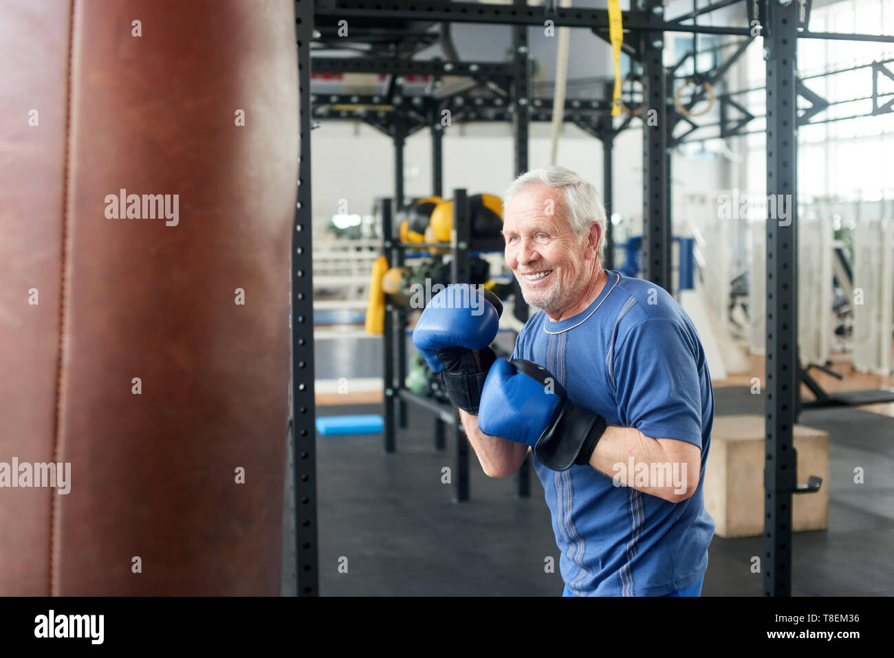 Handsome senior male training with punching bag. Old trainer training with punching bag in fitness studio. People, sport, active way of life. - Stock Image