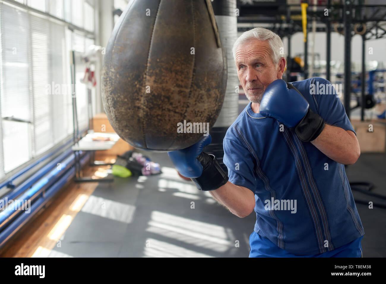 Elderly man hitting punching bag in boxing studio. Senior caucasian man in gloves beats punching bag in gym. - Stock Image