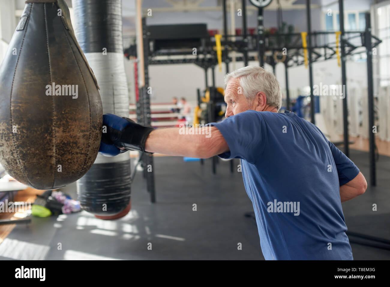 Mature man boxing punching bag. Senior caucasian sportsman boxing with punching bag at gym. - Stock Image