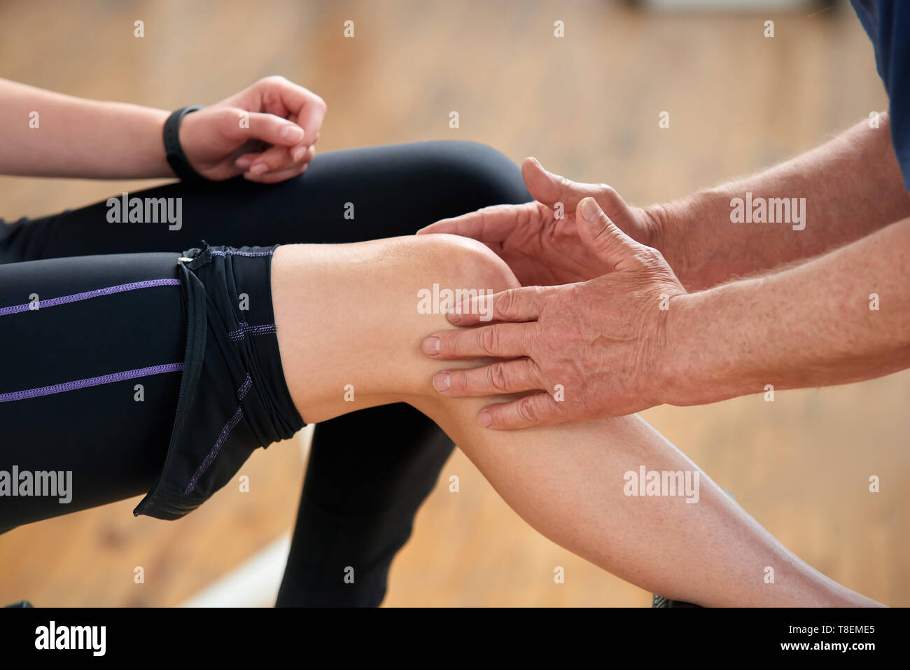 Muscle strain during workout. Male hands doing a massage to female knee at gym close up. Treating muscle soreness after sport exercise. - Stock Image