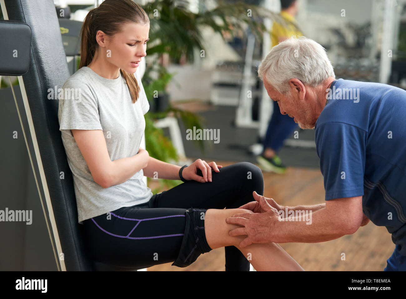 Athletic injured woman at gym. Senior male fitness instructor examining injured leg and knee of woman at fitness club. Muscle soreness after workout. - Stock Image