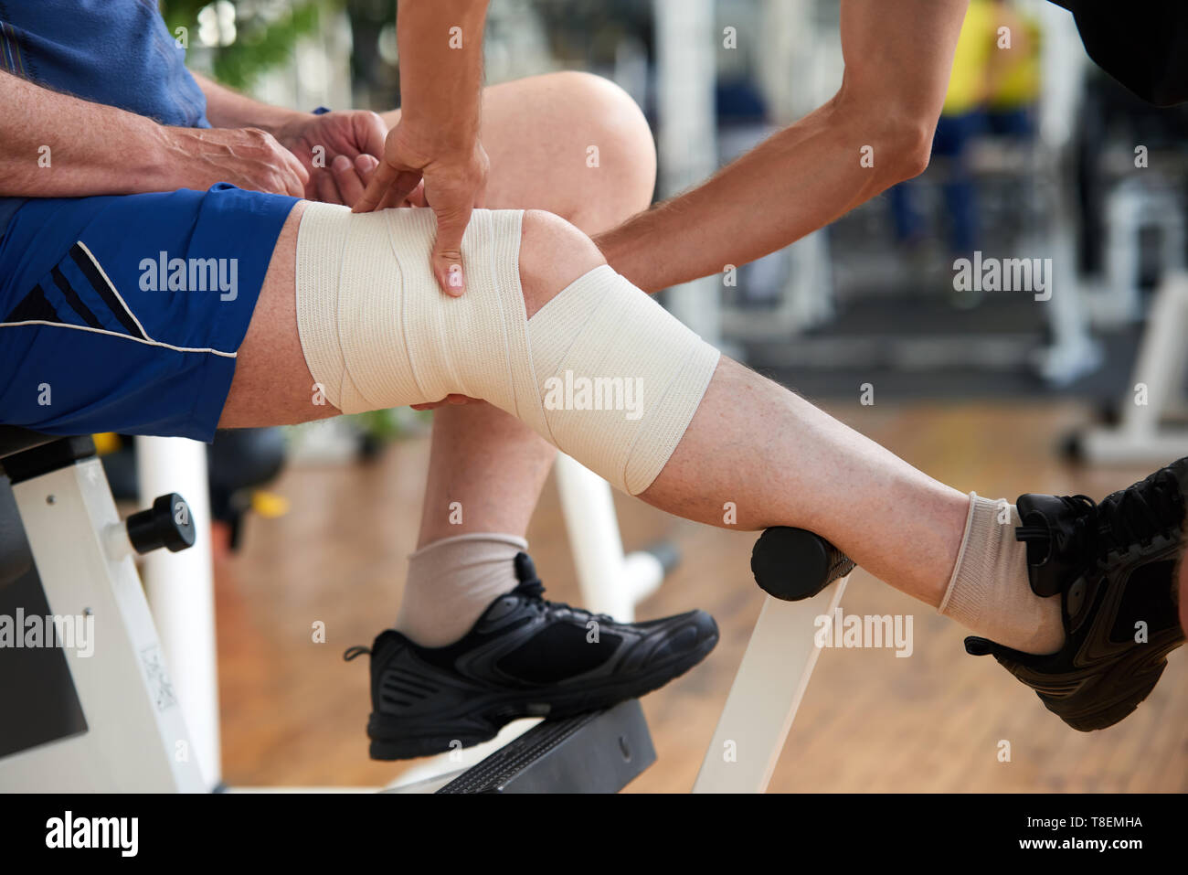 Wrapping Knee Injury Male Hands Fixed Elastic Bandage On Mans