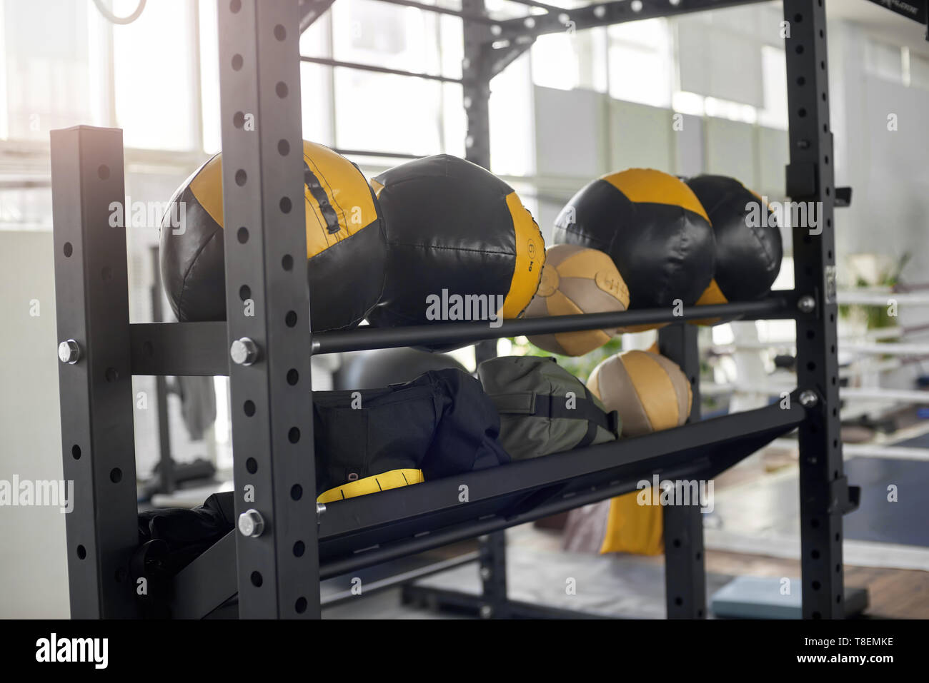 Rack with round punching bags at gym. Equipment for boxing at sport club. Set of modern fitness gym. - Stock Image