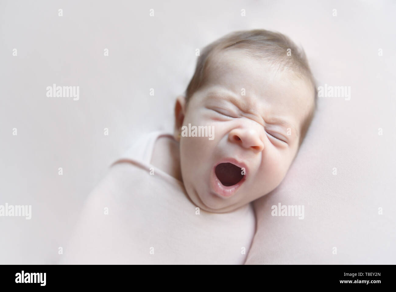 Newborn baby girl yawning lying in a pink blancket - Stock Image