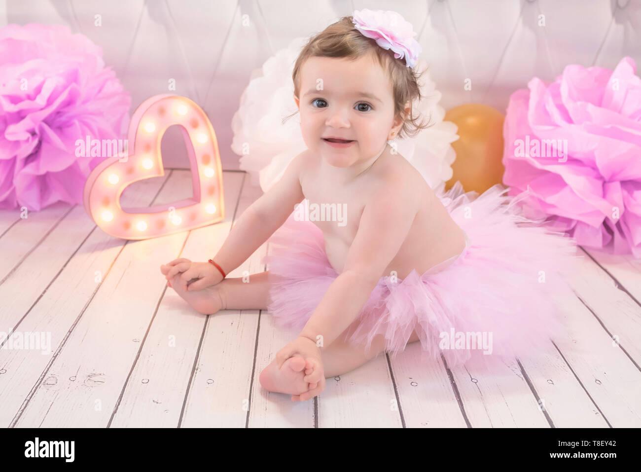 Portrait baby girl in tutu tulle skirt and headband celebrating her first birthday. Child kid sitting on floor. Natural light. Cake smash. - Stock Image