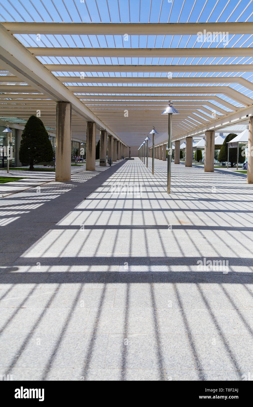 The courtyard at the airport, a place to smoke and wait for boarding outdoors. Modern architecture with metal columns and beams. Decorated with conifers, small lawns and gazebo. - Stock Image