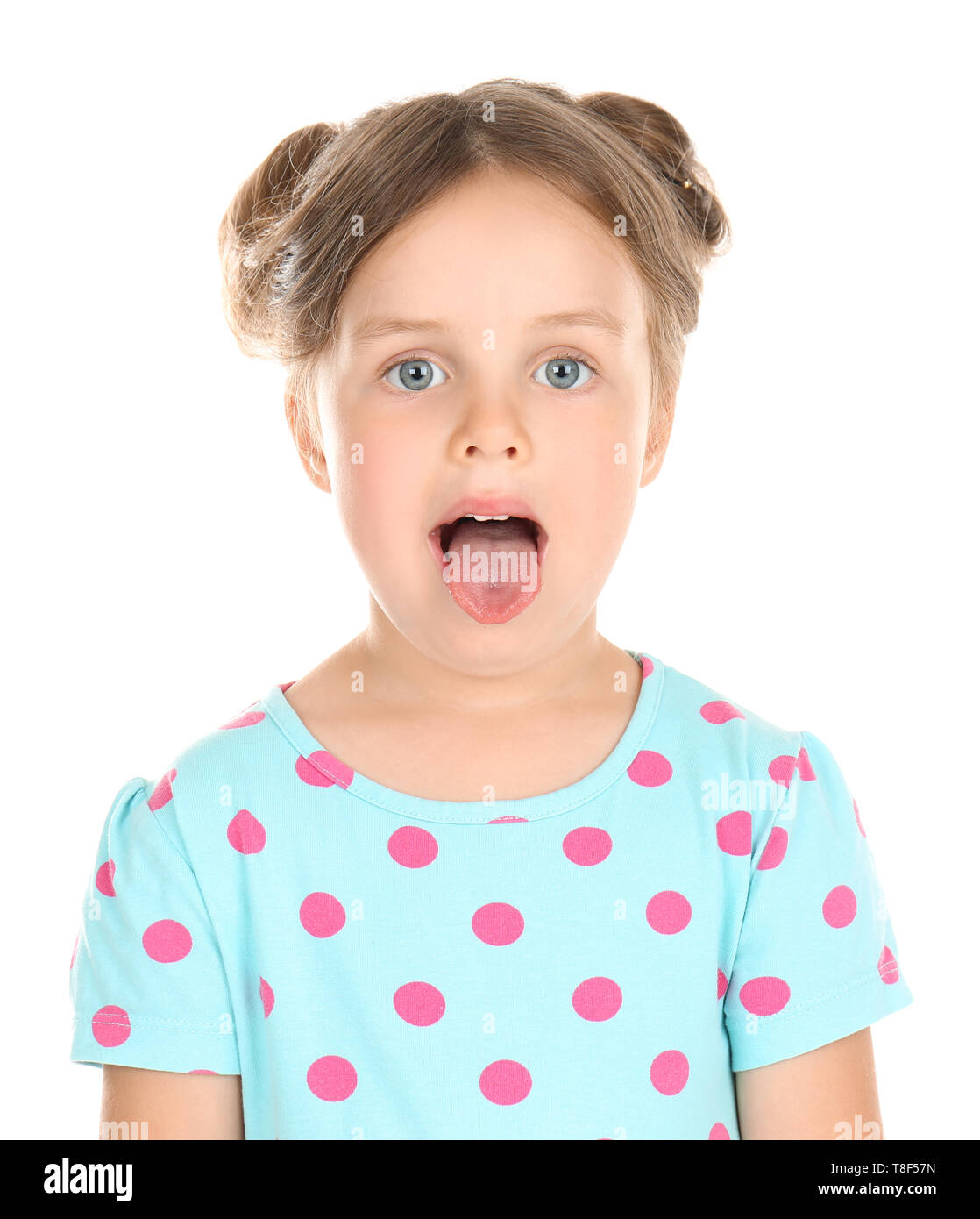 Cute little girl showing tongue on white background - Stock Image