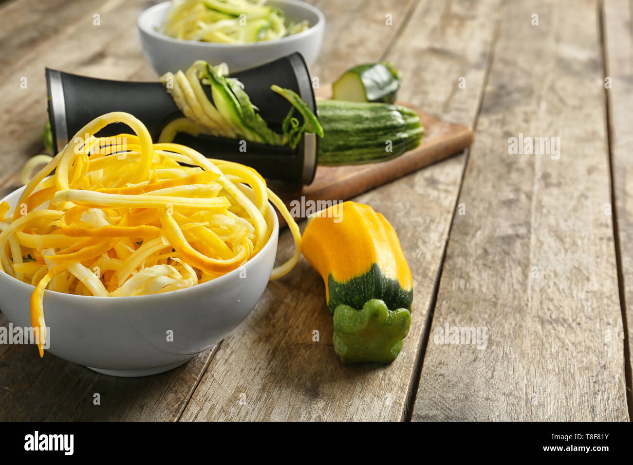 Fresh zucchini spaghetti with spiral grater on wooden table Stock Photo