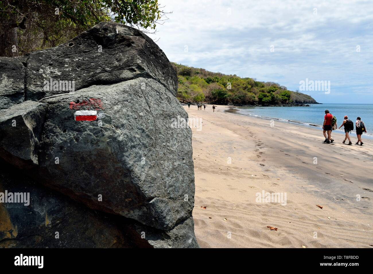 France, Mayotte island (French overseas department), Grande Terre, M'Tsamoudou, Saziley beach, hikers walking on the beach along the long distance hiking trail going around the island - Stock Image