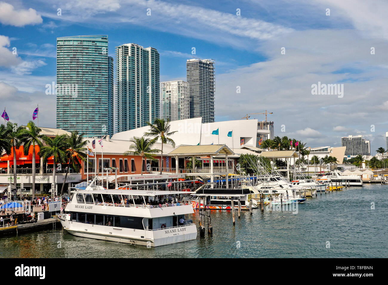 Miami, USA - February 22, 2016: ships with tourists on water in city harbor and skyscrapers on blue sky background at bayside, Miami. Summer vacation and cruising. Travelling and adventure. - Stock Image
