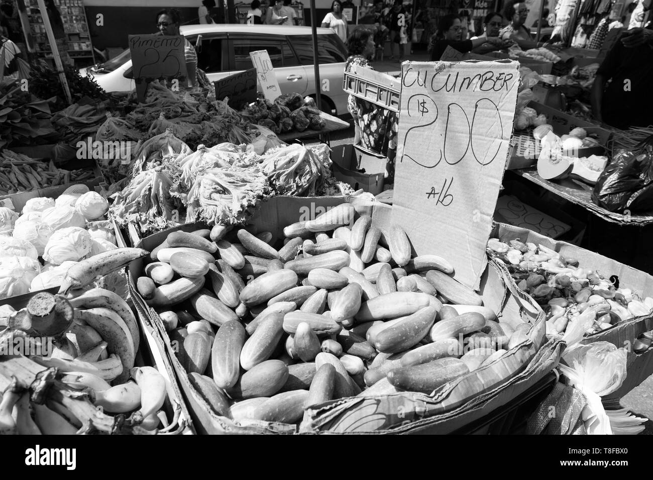 Port of spain, Trinidad and Tobago - November 28, 2015: Fresh vegetables and fruit ripe agricultural crop displayed for trade outdoors on market on streetscape background - Stock Image
