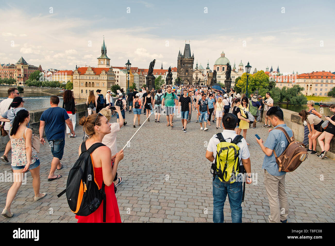 Prague, Czech Republic - June 03, 2017: people on Charles bridge over Vltava river with statues, towers, houses on blue sky. Tourist destination, travelling, wanderlust, vacation concept - Stock Image
