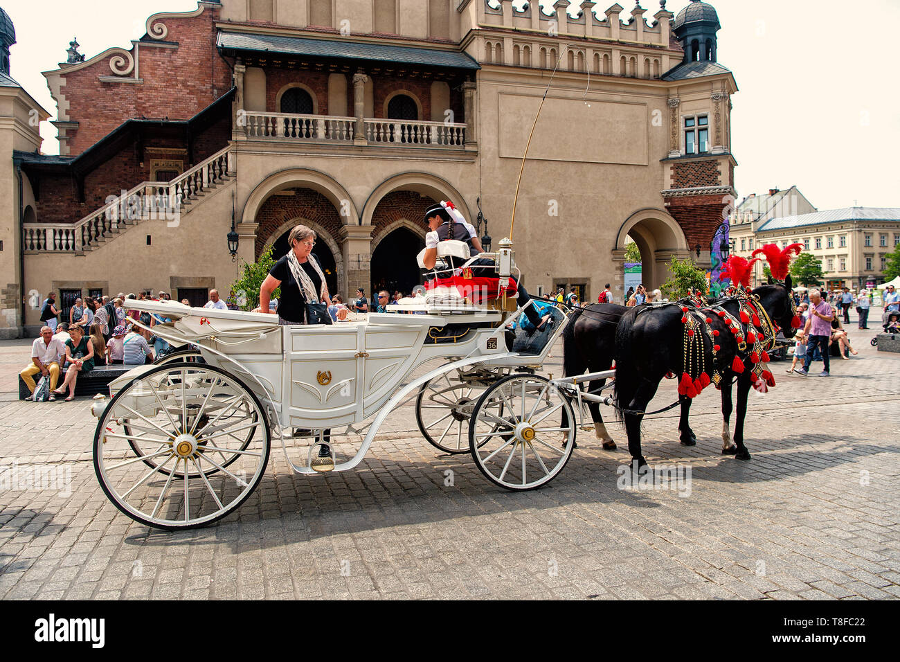 Krakow, Poland - June 04, 2016: tourist woman sit in white carriage with black horses in city square. Vacation, tour, travelling, discovery concept. - Stock Image