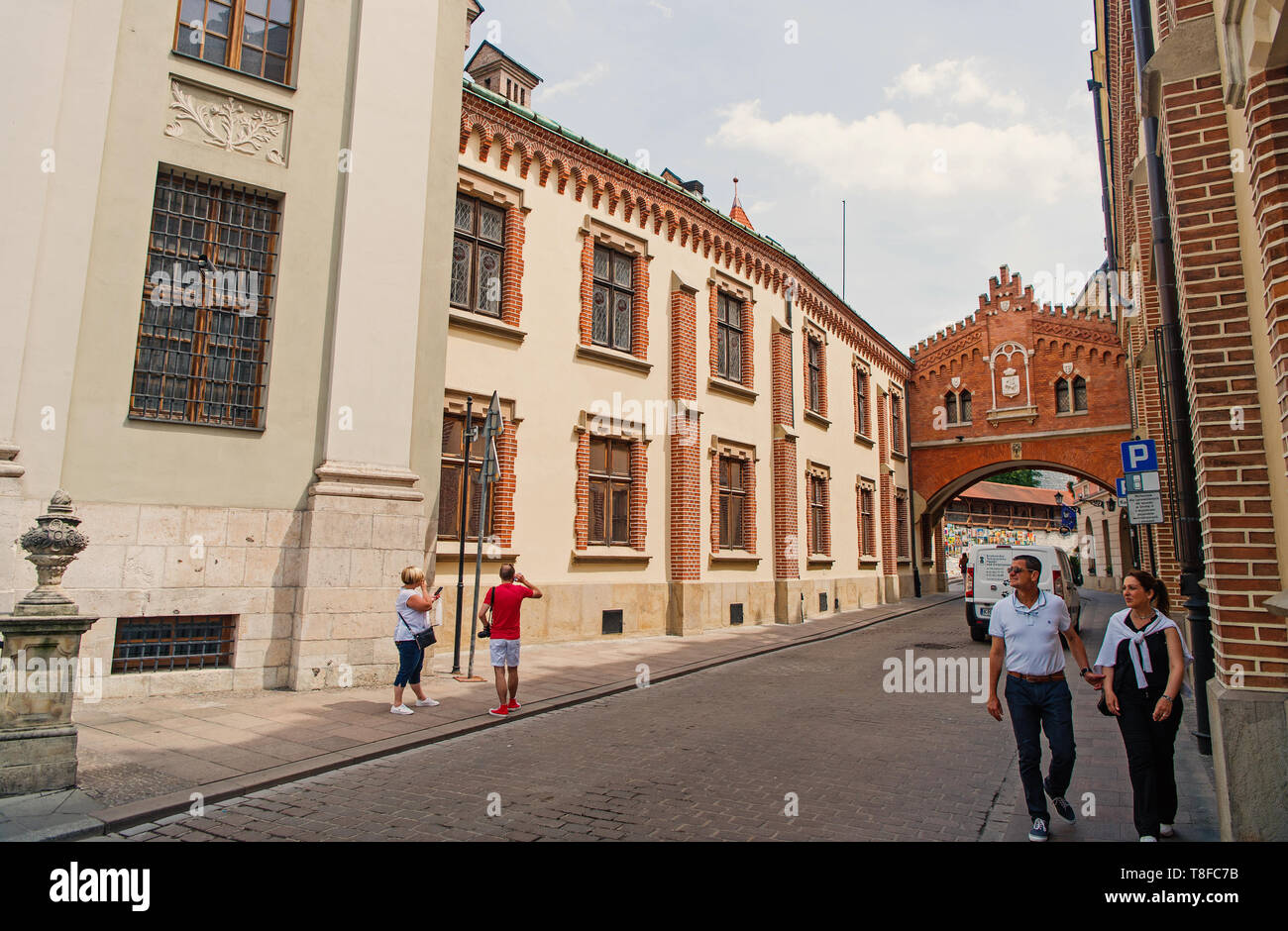 Krakow, Poland - June 04, 2016: people walk on street in city centre with old buildings on sunny day. Tourist destination, vacation concept - Stock Image