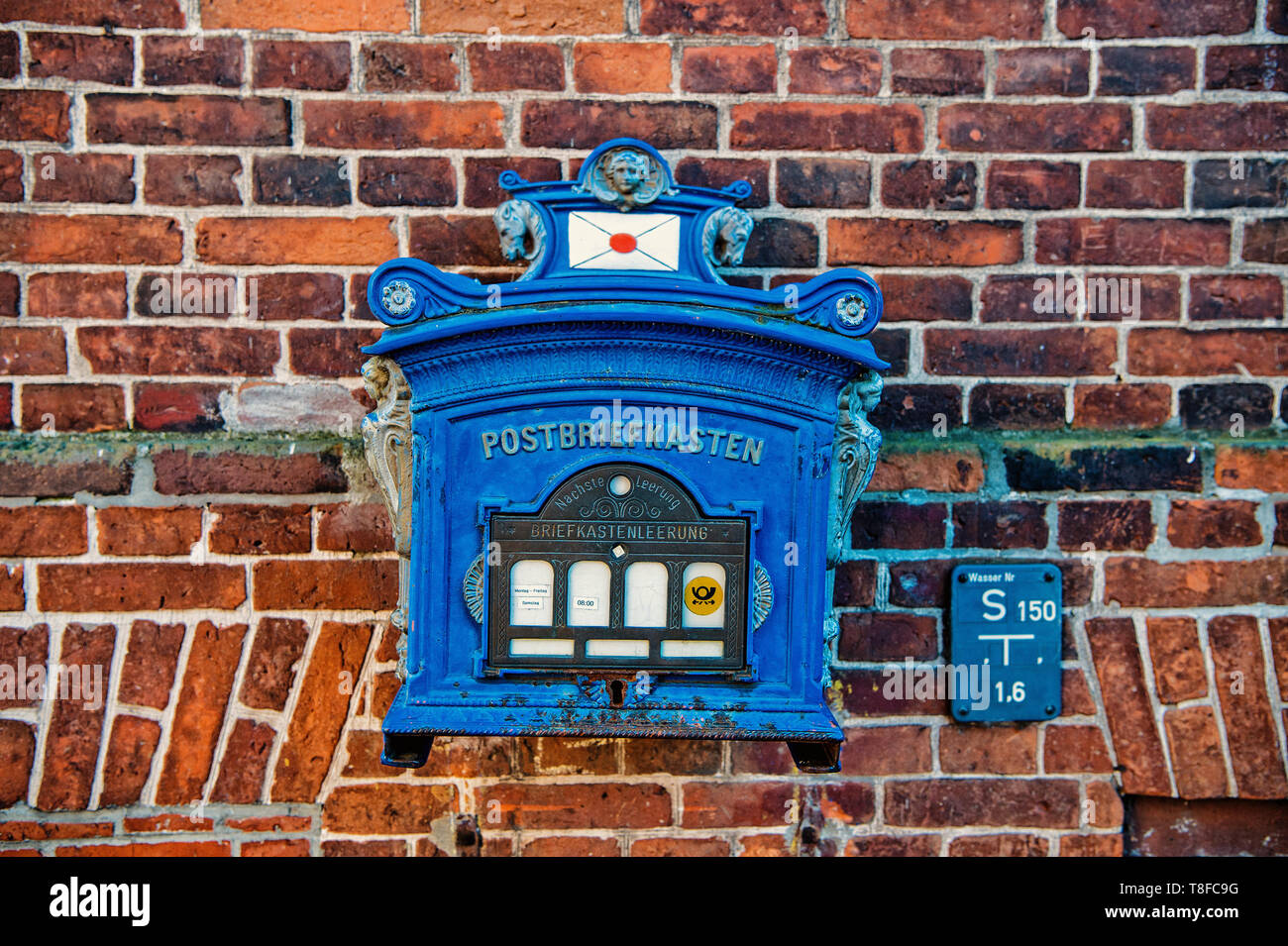 Post box of blue painted metal on red brick wall background. Correspondence, collection, delivery, mail, service concept. - Stock Image