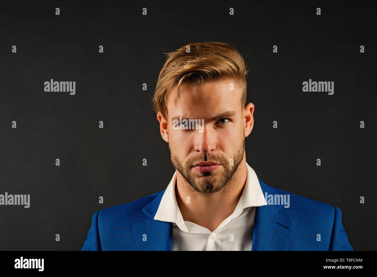 Feeling stressed after hard working day. Man bearded strict unhappy face looks untidy exhausted, dark background. Workaholic concept. Man unshaven guy looks stressed after stressful business meeting. - Stock Image