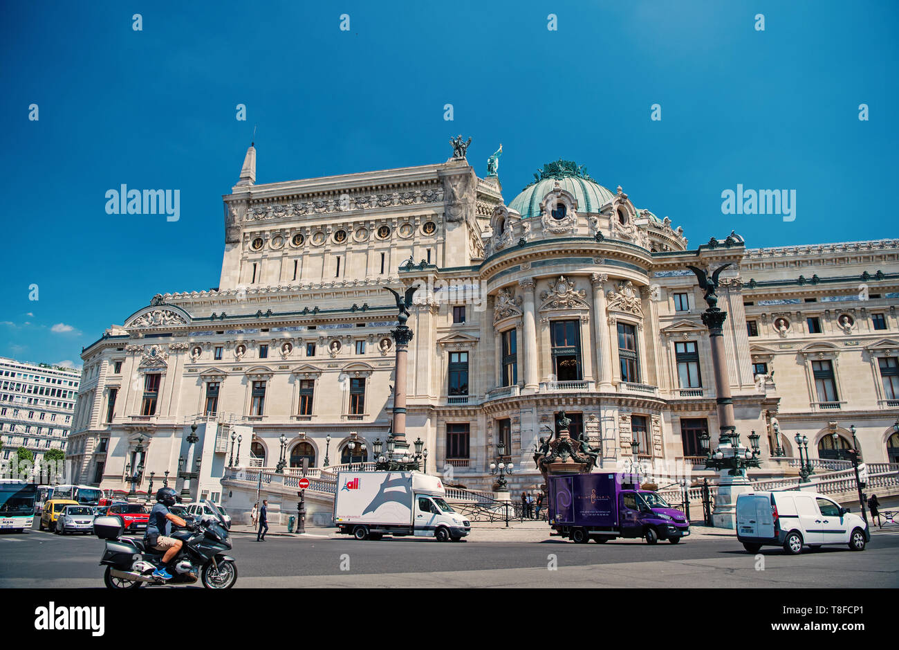 Paris, France - June 01, 2017: Garnier palace or opera house building on sunny blue sky background. City street traffic. Landmark and sightseeing. Classic music and art concept - Stock Image