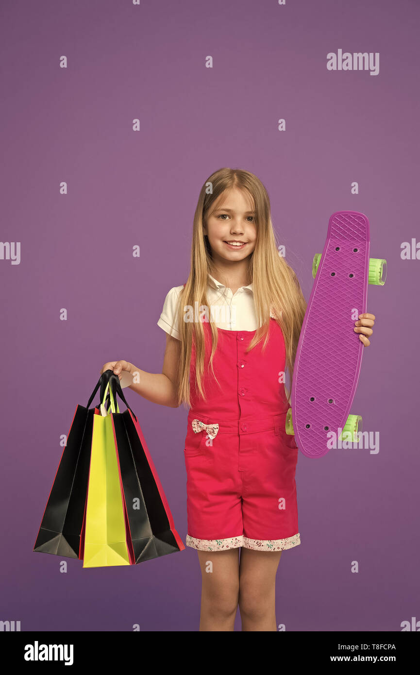Happy girl with skate board and shopping bags on violet background. Little child smile with paper bags and skateboard. After day shopping. sale and black friday. Sport and active games. - Stock Image