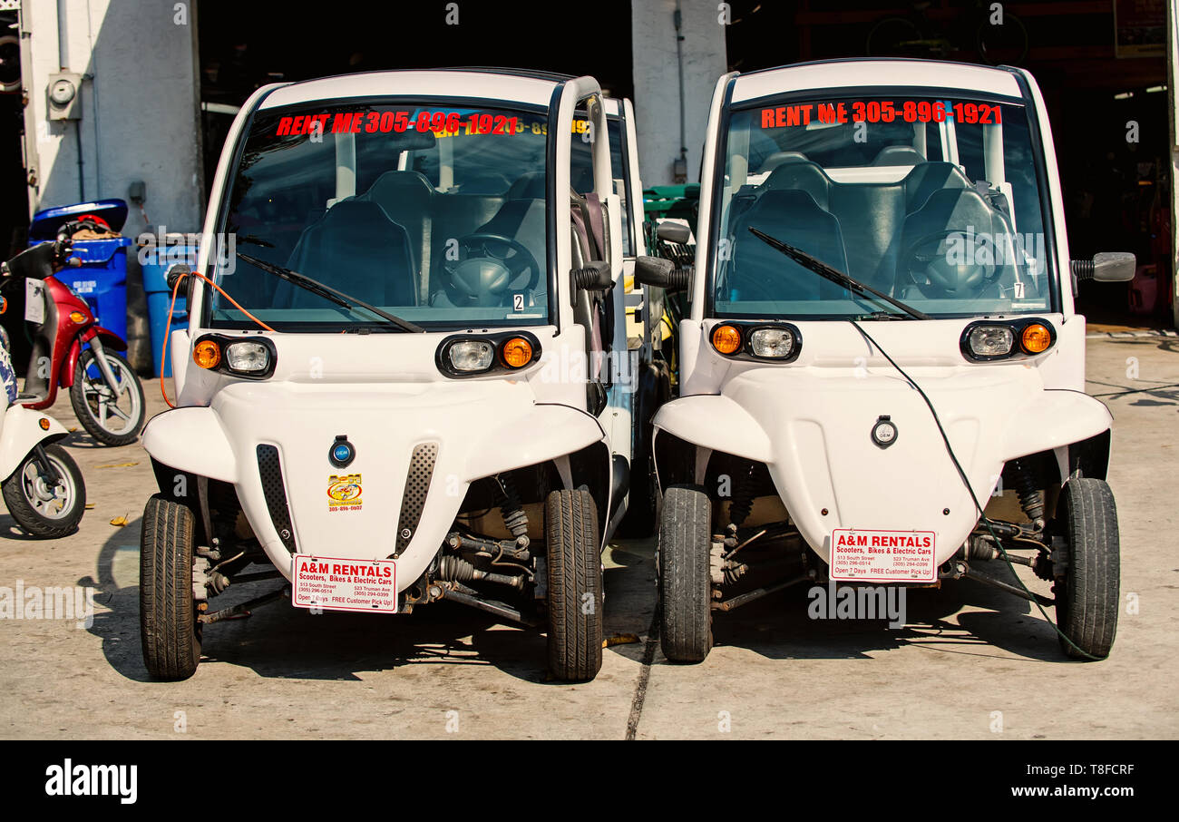 Key West, USA-december 26. 2015 : Two electric cars on garage background in Key West, USA. White carts or automobiles on sunny day. Summer holiday and travelling. Active lifestyle concept. Rent car - Stock Image