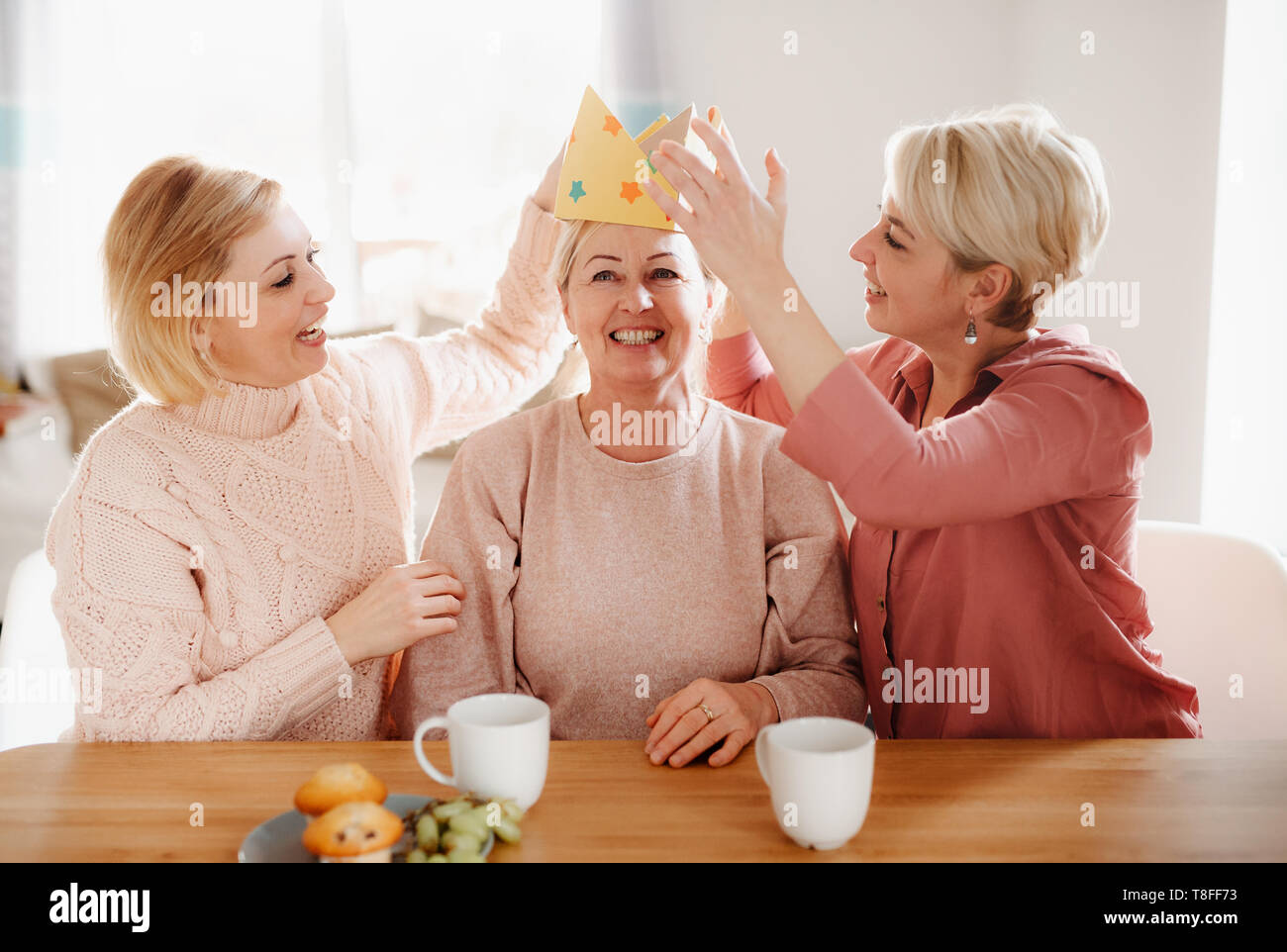 A senior mother with two adult daughters sitting at the table at home, having fun. - Stock Image