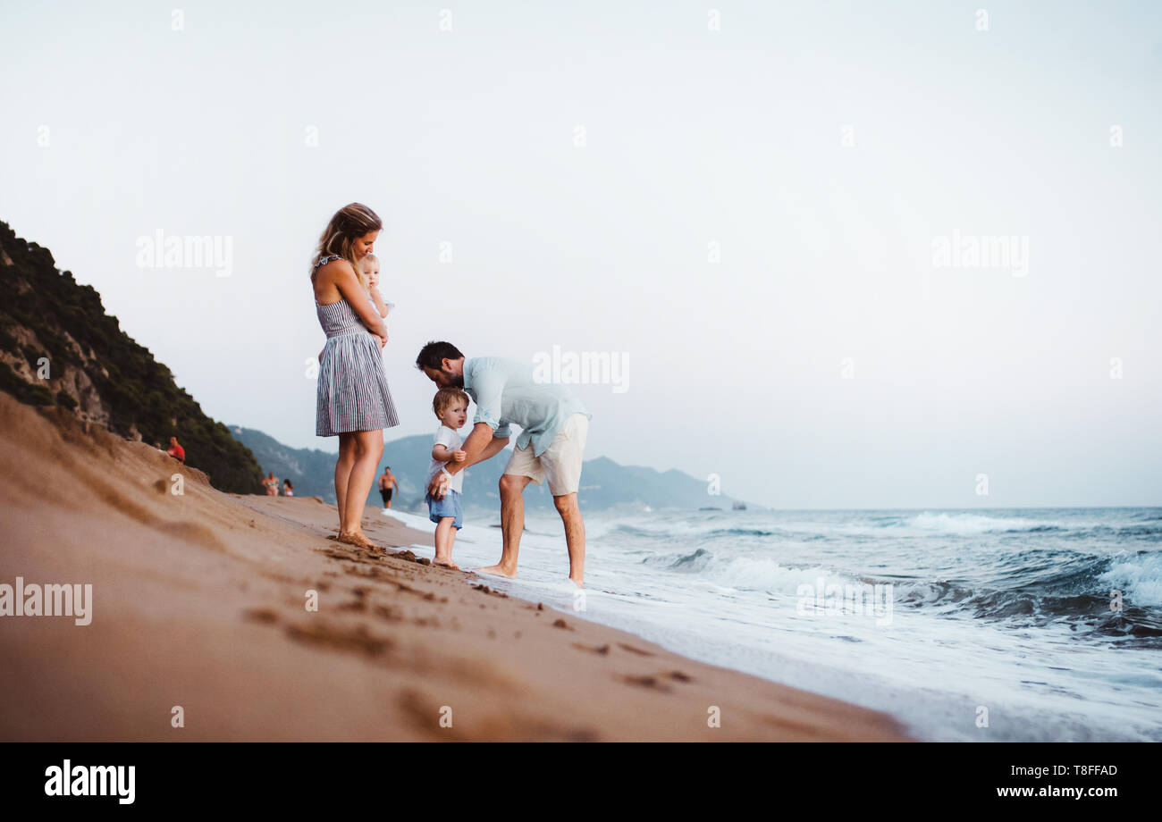 A young family with two toddler children standing on beach on summer holiday. - Stock Image